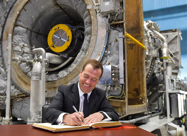 Russia's Prime Minister Dmitry Medvedev signs the distinguished visitors' book as he visits the Nevsky Zavod machine-building plant, May 16
