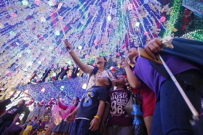 """Filipinos pose for souvenir shots at the """"Christmas House"""" in suburban Cainta, Rizal province east of Manila, Philippines"""