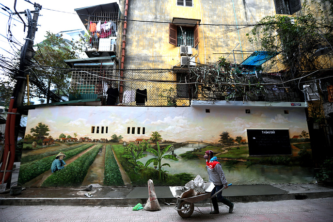 A woman walks past a painted wall at the collective zone of Vietnam women's academy, in Hanoi, Vietnam, January 10
