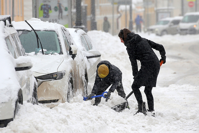 A woman digs up her car during heavy snowfall in Moscow