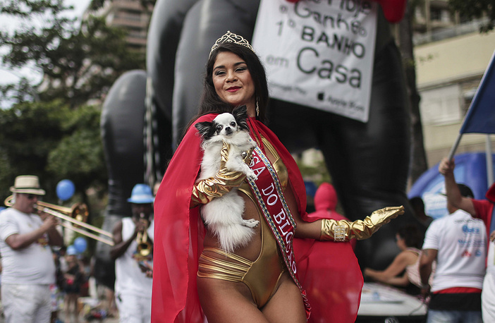The queen of the Blocao troupe carries a dog during the Carnapet Parade, at the Copacabana beach, Rio de Janeiro