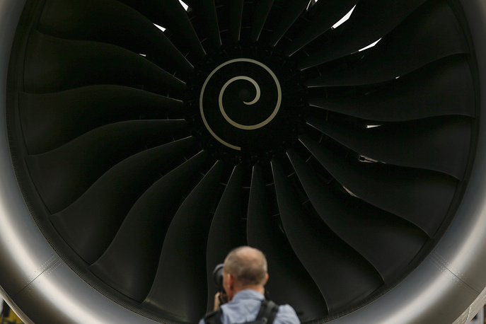 A visitor takes a photo of the Rolls-Royce jet engine of the Airbus A350-1000