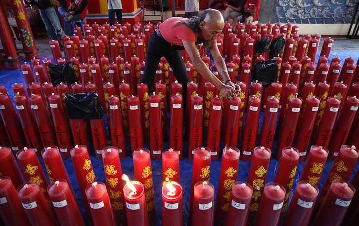 An Indonesian ethnic Chinese worker arranges candles during preparations for the Chinese New Year at a temple in Bogor, Indonesia