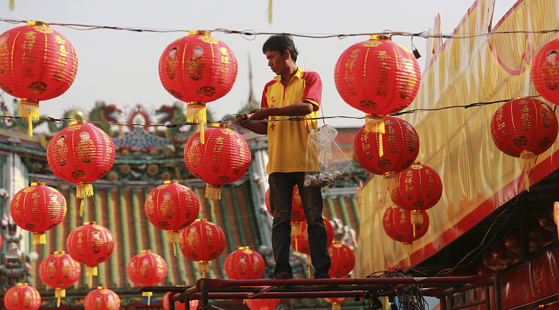 A Thai worker decorates lanterns for celebrations of Chinese New Year at the Leng Nuei Yee Chinese temple in Bangkok, Thailand
