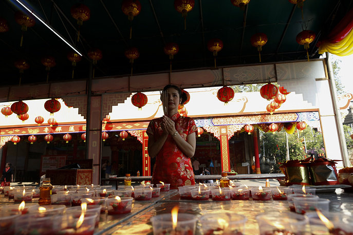 A woman prays with incense and joss sticks for good fortune to mark the Chinese Lunar New Year at Leng Noei Yi Temple or Dragon Lotus Temple in Chinatown, Bangkok, Thailand