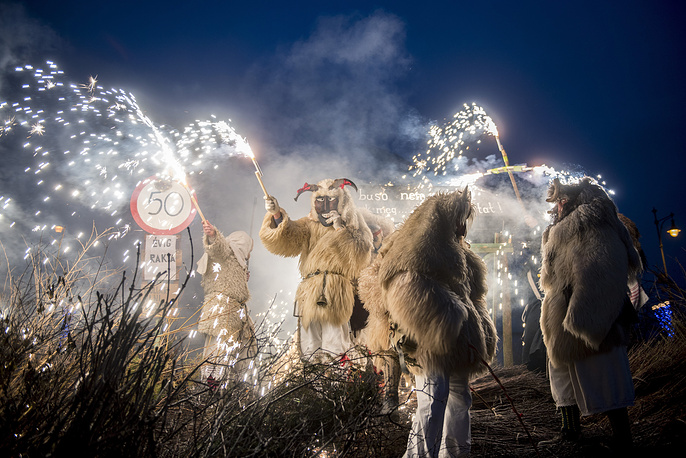 Revelers wearing sheepfur costume lit a bonfire to burn a coffin, symbolizing winter, during the closing ceremony of the traditional carnival parade in Mohacs, Hungary, February 13