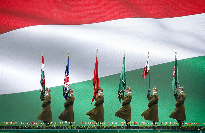 Hungarian soldiers march, backdropped by a large display showing Hungary's national flag during a ceremony celebrating the Hungarian national holiday, the 170th anniversary of the outbreak of the 1848 revolution and war of independence against the Habsburgs, Budapest, Hungary, March 15