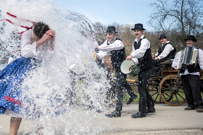 Young men, Dressed in Bukovina Szekler folk costumes, pour water on young women in Ciko, Hungary, April 2. According to an old Hungarian tradition young men pour water on young women, who in exchange present their sprinklers with beautifully colored eggs on Easter Monday
