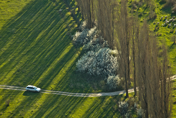 An aerial view of a car moving by the White Rock in Belogorsky district
