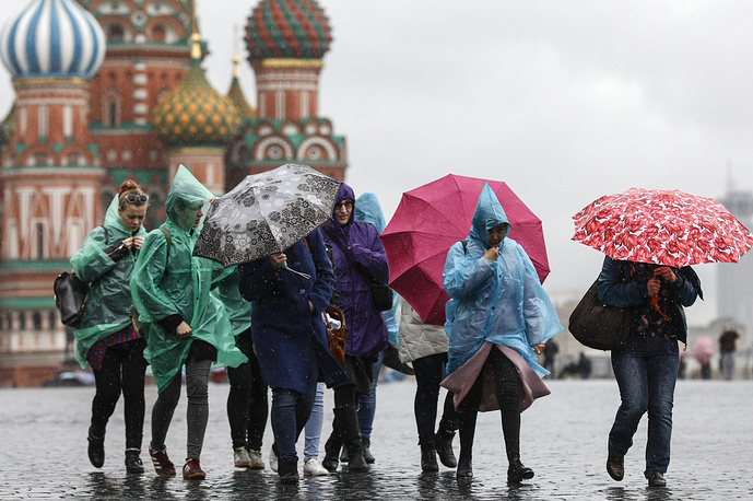 Tourists under umbrellas during a rain shower in Moscow's Red Square, April 18