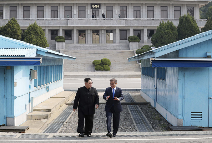 North Korean leader Kim Jong Un listens to South Korean President Moon Jae-in while walking together at the Panmunjom