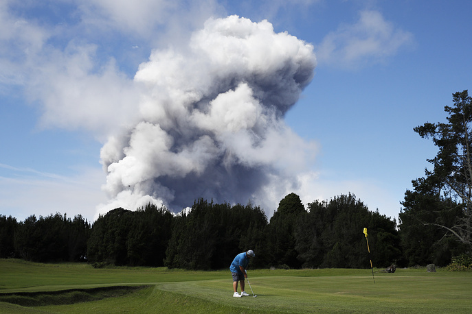 A man plays golf as a huge ash plume rises from the summit of Kiluaea volcano