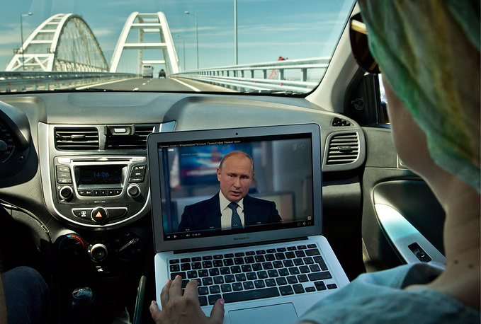 A Russian passenger tunes in to watch a live broadcast of Russian President Vladimir Putin's annual question and answer session on a laptop in a car, Crimea, June 7