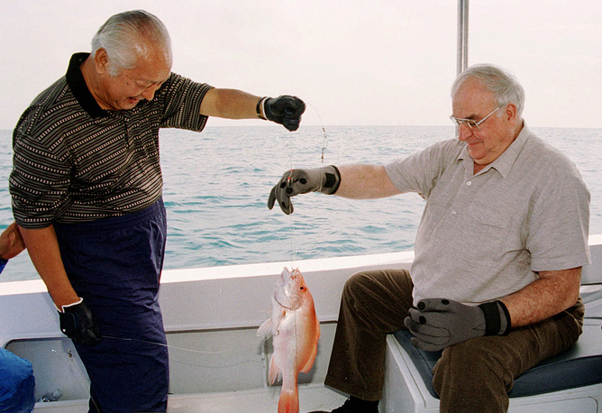 German chancellor Helmut Kohl and Indonesian President Suharto jointly admire a fish they caught off the coast of island Bira near Jakarta, 1996