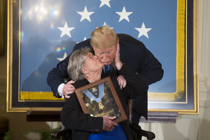 Widow of US Army First Lieutenant Garlin Conner, Pauline Conner kisses US President Donald J. Trump after being presented with the Medal of Honor for her late husband who was awarded the nation's highest military decoration for his actions on January 24, 1945; during a ceremony in the East Room of the White House in Washington, June 26. Then-US Army First Lieutenant Garlin Conner volunarily left a position of relative safety to direct friendly artillery shells, which drove back an enemy assault and saved numerous American lives