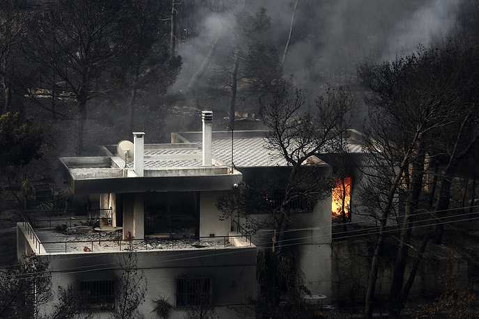 A view of a burning house during a fire in Neo Voutza, northeast Attica