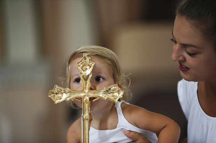 A girl kisses the gold plated cross in the church of the Black Madonna, during the feast of Assumption in the village of Letnica, August 15. Thousands of pilgrims gathered in southeastern Kosovo in the small Roman Catholic community where Mother Teresa is believed to have heard her calling to become a nun