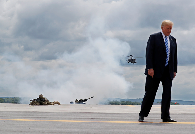 US President Donald Trump attends a drill by the US Army's 10th Mountain Division troops, with an attack helicopter and artillery in the background at Fort Drum, New York, August 13