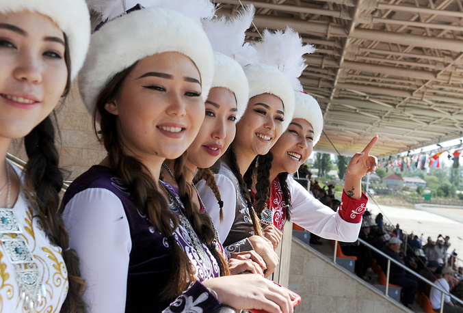 Young women in traditional costumes watching 2018 World Nomad Games