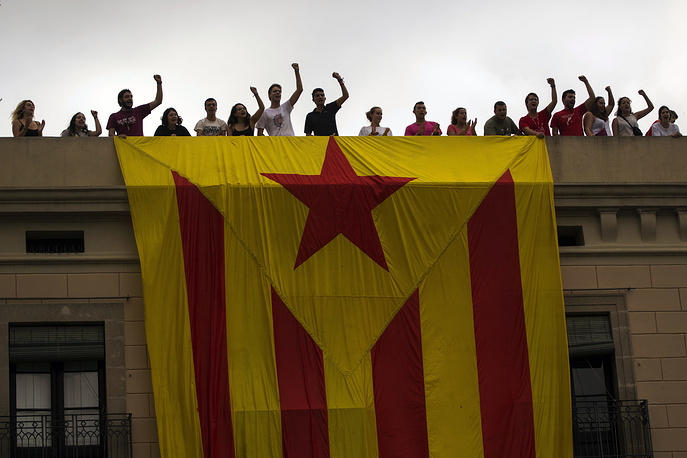 "People react as they roll out a giant ""estelada"" or independence flag on top of a building during the Saint Merce celebrations in Barcelona"