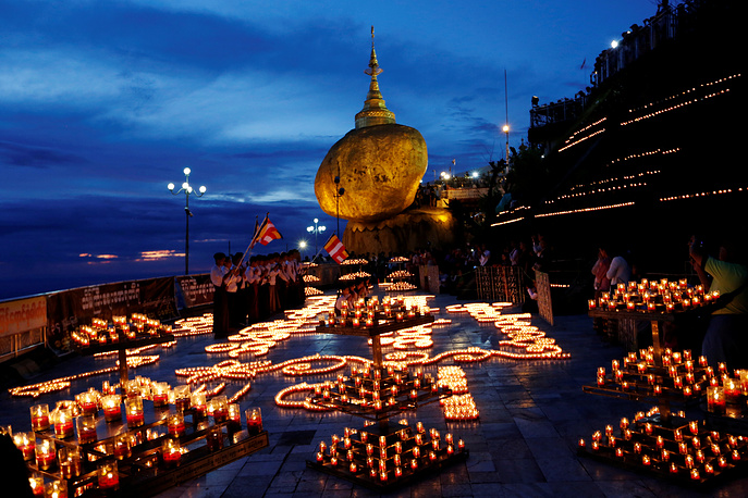 Buddhist pilgrims light candles around the Golden Rock or Kyaikhtiyo Pagoda to celebrate the full moon festival in Kyaikto, Myanmar, October 24