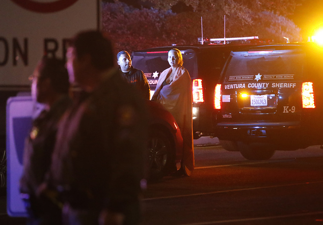 A woman wearing a blanket stands next to a police office near the Borderline Bar and Grill in Thousand Oaks