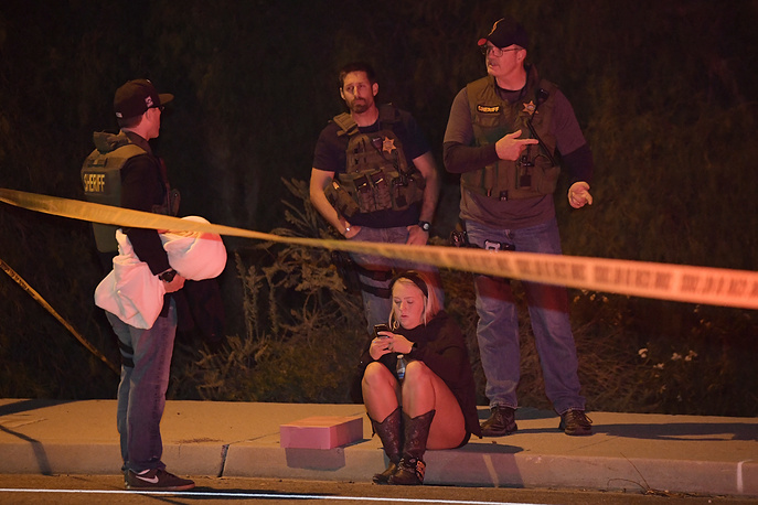 Sheriff's deputies speak to a potential witness as they stand near the scene in Thousand Oaks, where a gunman opened fire inside a country dance bar