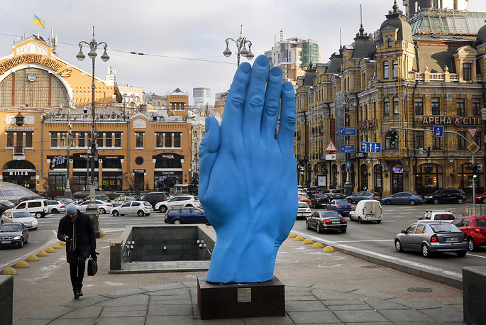 """A man passes at the displayed art installation """"Middle way"""" by Romanian artist Bogdan Rata in Kiev, November 20"""
