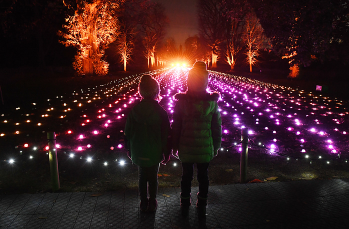 Young girls look over part of Kew Gardens' illuminated Christmas trail, 'a field of light' at Kew Gardens in London, November 21