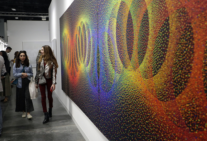 """People walk past a painting by Julio Le Parc titled """"Alchimie 396"""" displayed at the Nara Roesler Gallery at Art Basel, Miami Beach"""