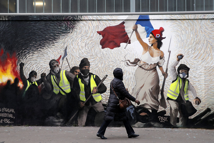 "A woman passes by a mural by street artist PBOY depicting Yellow Vest (gilets jaunes) protestors inspired by a painting by Eugene Delacroix, ""La Liberte guidant le Peuple"" (Liberty Leading the People), in Paris, January 10"