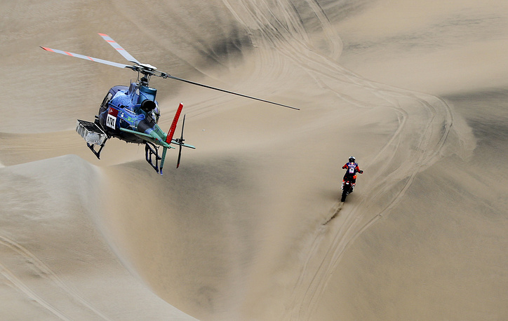 Luciano Benavides of Argentina rides his KTM motorbike followed by a TV helicopter during stage six of the Dakar Rally between Arequipa and San Juan de Marcona, Peru