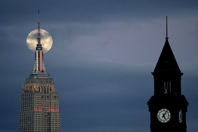 A super moon is seen in its waxing gibbous stage behind the Empire State Building, with the Lackawanna rail and ferry station tower seen at right, Jersey City