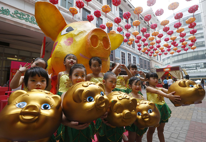 Girls display piggy banks at the start of celebrations leading to the Lunar New Year at Manila's Lucky Chinatown Plaza in Manila