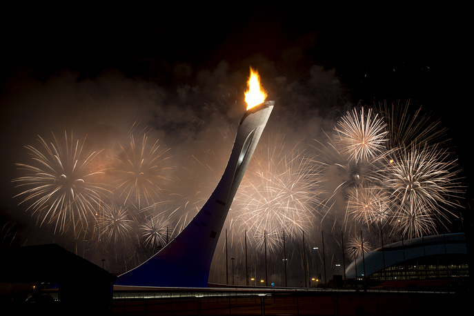 Fireworks exploding behind the Olympic torch, announcing the official opening of the Sochi Winter Olympics