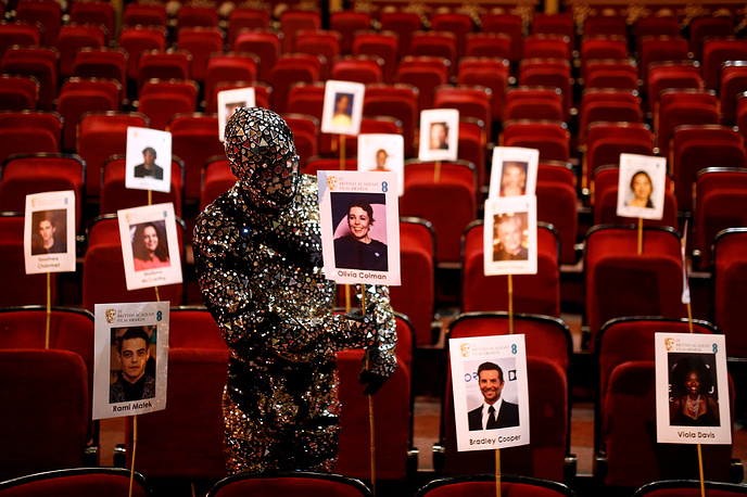 A Cirque du Soleil cast member displays a place stick for a guest during preparations for the British Academy of Film and Television Awards ceremony at the Royal Opera House in London, February 7