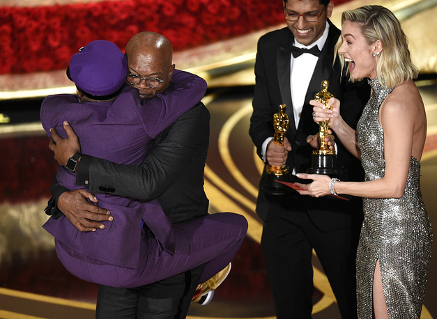 "Samuel L. Jackson embraces Spike Lee, winner of the award for best adapted screenplay for ""BlacKkKlansman"" as Brie Larson looks on, at the Dolby Theatre in Los Angeles"