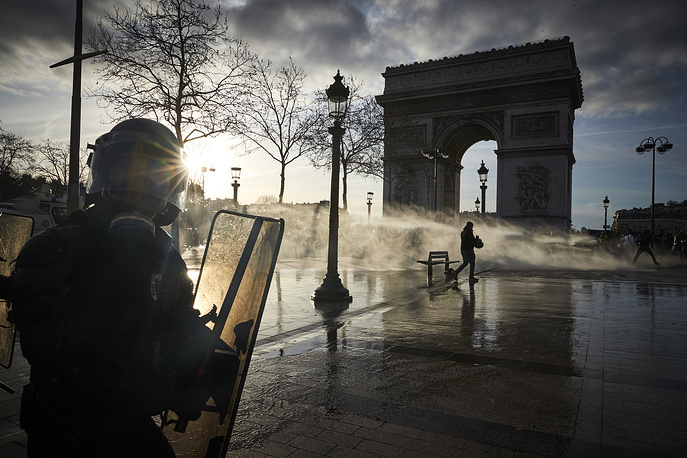 French Riot Police use water canon to disperse Gilets Jaunes or 'Yellow Vests' protestors by the Arc de Triomphe during Act 16 of demonstrations in Paris, March 2. Yellow Vests movement started as a protest against a rise in Fuel tax and living