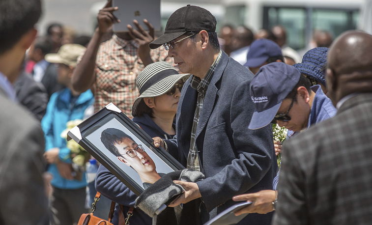 A family member holds a framed photo of loved one at the scene where the plane crash near Bishoftu in Ethiopia