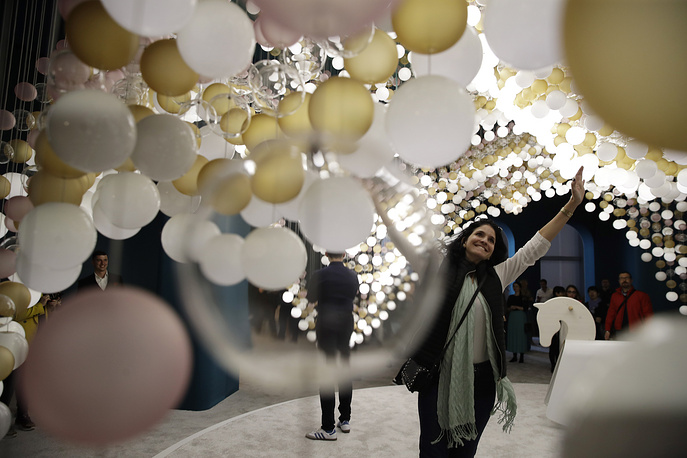 A visitor enjoys 'Carusel of Lights', an interactive lighting creation for Preciosa by creative director Michael Vasku, displayed at the Salone del Mobile Furniture Fair, in Rho, near Milan, Italy