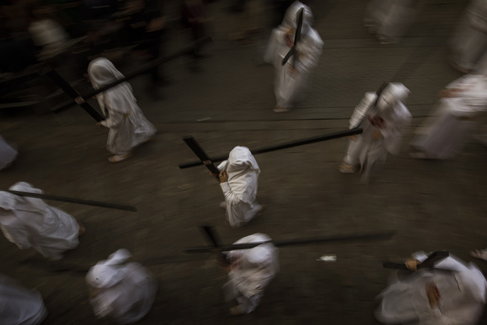 "Hooded penitents from ""La Amargura"" brotherhood carrying their crosses in Seville"