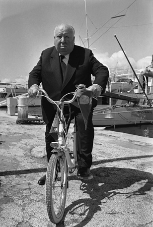Master of suspense film director Alfred Hitchcock pedals his bicycle in Cannes, 1972