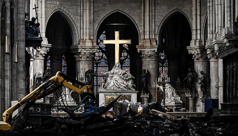 Rubble and the cross at the altar inside the the Notre Dame de Paris Cathedral after it sustained major fire damage the previous month