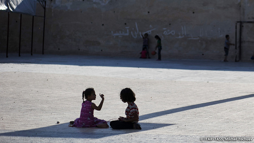 September 19. Refugee children hide in the shadow on a playground of a local school-turned-shelter.