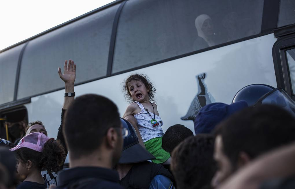 Migrants trying to board a bus, at the border between Serbia and Croatia AP Photo/Manu Brabo
