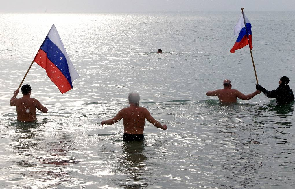 Crimean residents bath in the Black Sea holding Russian national flags (archive) Alexey Pavlishak/TASS