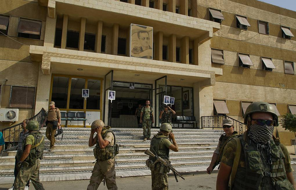 Russian military police soldiers walk out side a hospital in Deir el-Zor, Syria AP Photo