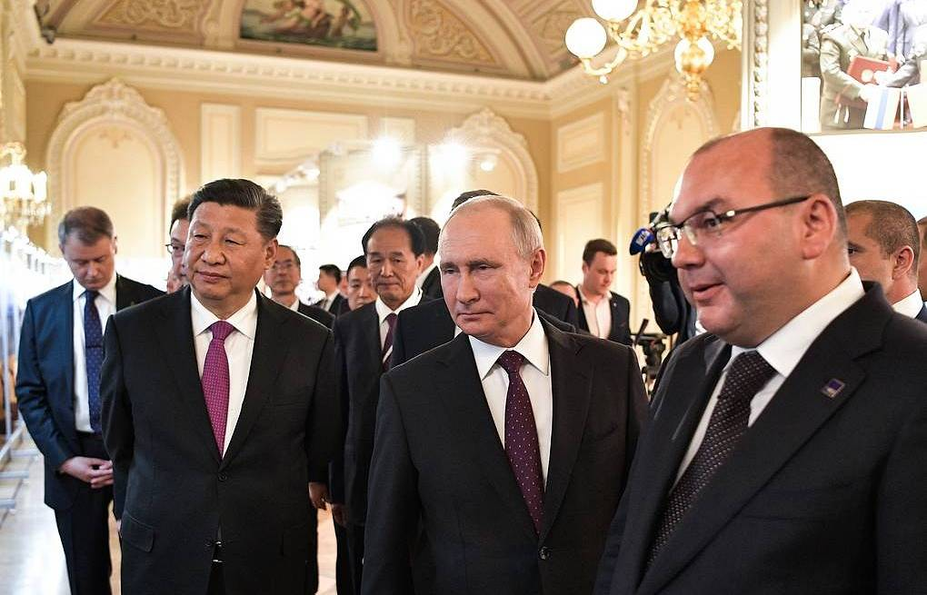 China's President Xi Jinping, Russia's President Vladimir Putin, TASS Russian News Agency General Director Sergei Mikhailov (L-R) view a photo exhibition titled 'Russia and China: 70 Years of Cooperation'  Alexei Nikolsky/Russian Presidential Press and Information Office/TASS