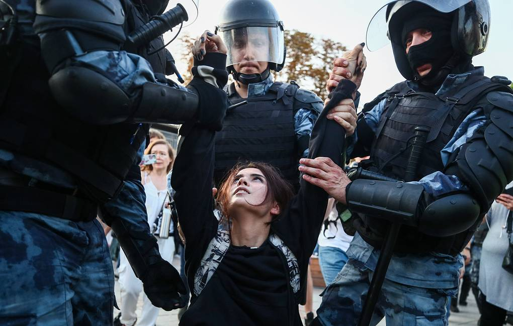 Police officers detaining a woman during an unauthorized protest in Moscow Sergei Bobylev/TASS
