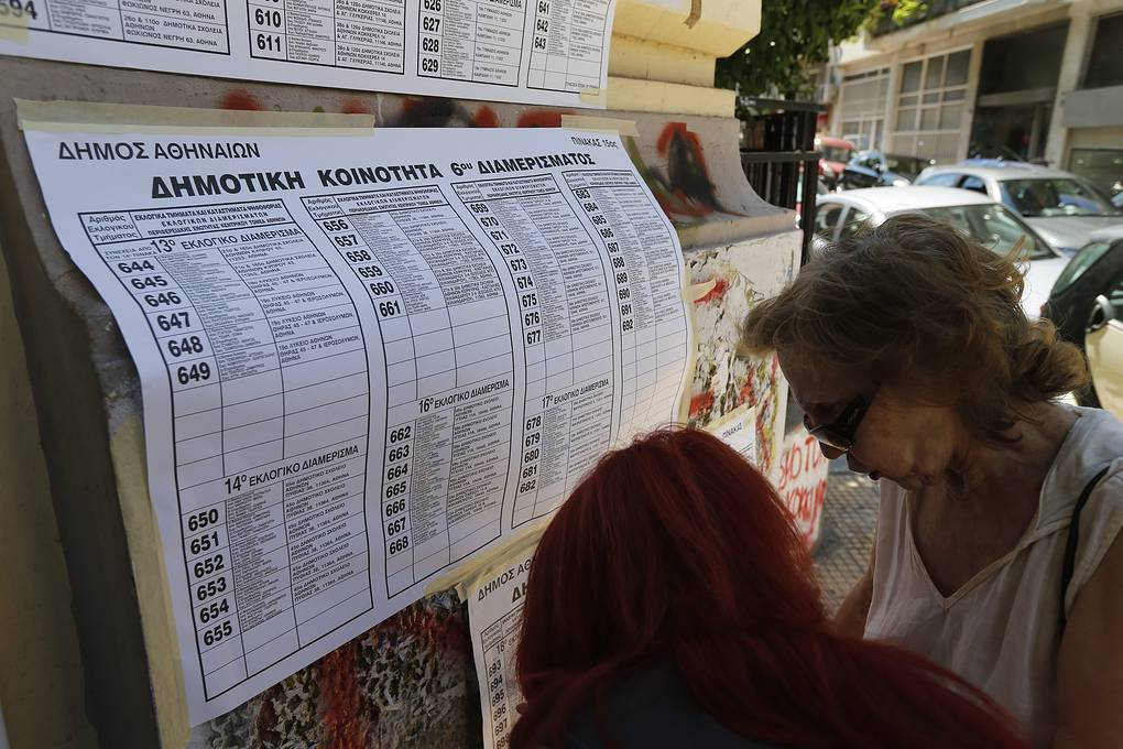 People try to find their names on a voting lists outside a voting centre during a referendum in Athens, Greece, 05 July 2015. Greek voters in the referendum are asked whether the country should accept reform proposals made by its creditors. EPA/ARMANDO BABANI